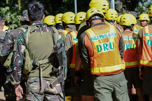 Philippine rescuers and soldiers take part in a morning prayer before starting retrieval operations in Ucab, Itogon, Sept. 18, 2018.