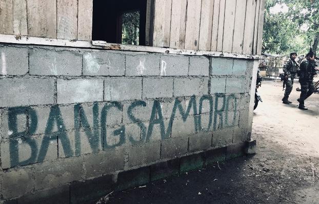 Moro Islamic Liberation Front fighters walk past a sign declaring the region Bangsamoro, June 22, 2019. (Jason Gutierrez/BenarNews)