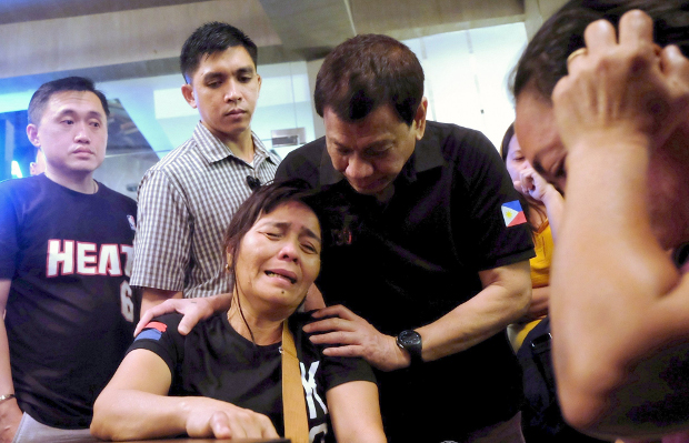 Philippine President Rodrigo Duterte comforts a relative of one of the victims of a fire that engulfed a shopping mall in Davao City, Dec. 23, 2017.
