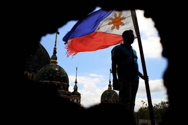 A tattered Philippine flag flutters in the wind near the pockmarked Grand Mosque in Marawi, May 16, 2018. (Richel V. Umel/BenarNews)