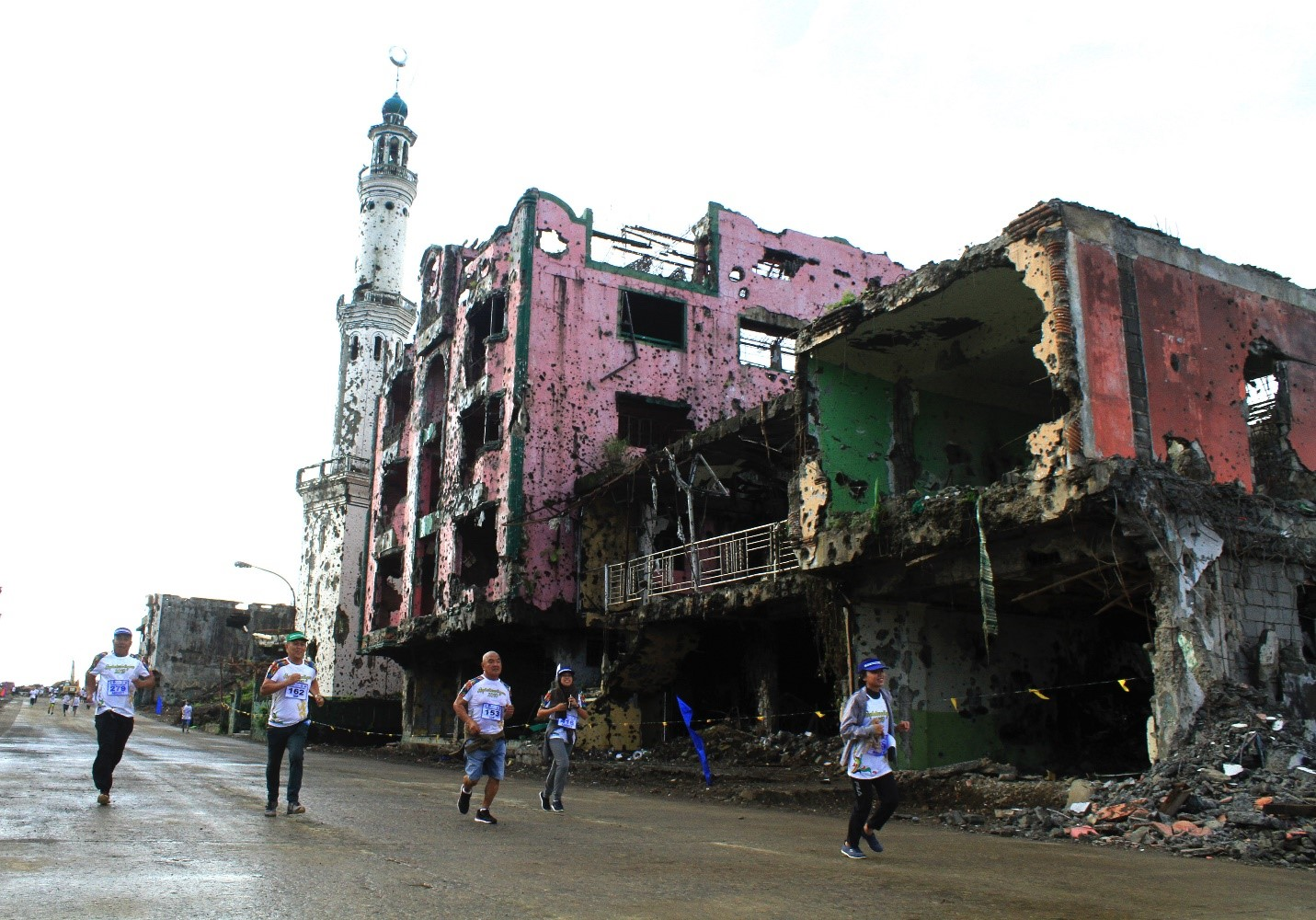 """Runners join a """"fun run"""" fundraiser in the ruined commercial district of Marawi, where Islamic State-linked militants engaged Philippine security forces in vicious firefights two years ago, Oct. 17, 2019. (Photo: Richel V. Umel/BenarNews)"""
