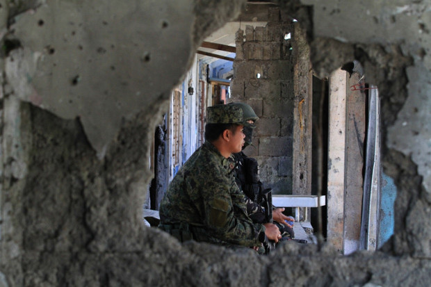 Soldiers watch as residents return to their ruined homes in southern Philippine city of Marawi, April 4, 2018. [Richel V. Umel/BenarNews]