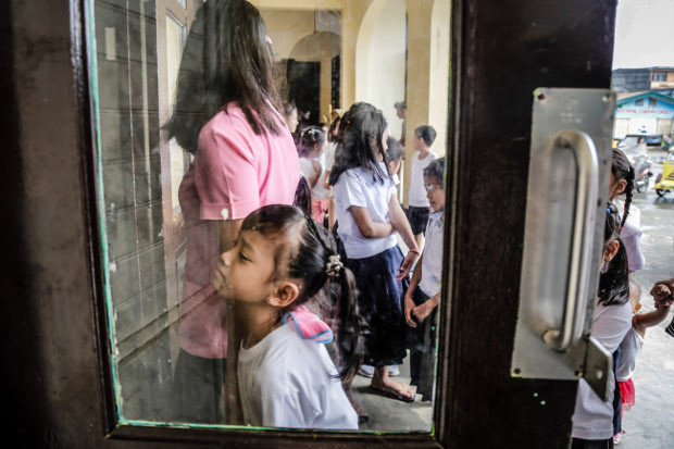Pupils line up at an immunization center at an elementary school to have free booster shots against diseases like measles, rubella, diphtheria, tetanus and HPV vaccine administered in Dagupan City, Philippines, Aug. 2, 2017. (Karl Romano/BenarNews)