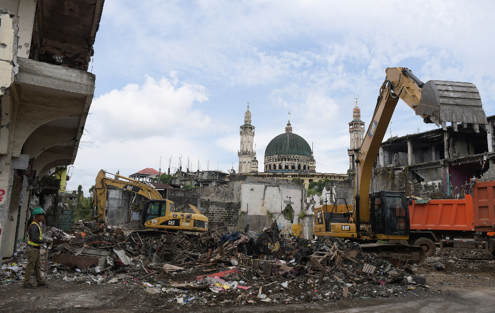 Excavators tear down buildings and clear debris in the southern Philippine city of Marawi in front of what remains of the city's Grand Mosque, Sept. 4, 2019.  (Photo: Froilan Gallardo/BenarNews)