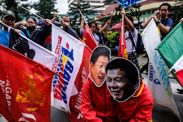 Members of the indigenous rights group Cordillera People's Alliance carry flags pointed at their fellow demonstrators wearing Duterte and Xi masks during a protest rally in the northern Philippine city of Baguio, July 22, 2019. [Jojo Rinoza/BenarNews]