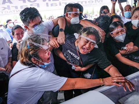 Relatives of Sonia and Frank Anthony, a mother and son who were shot dead by an off-duty policeman, bid goodbye to them at their funeral in Paniqui, Philippines, Dec. 20, 2020.