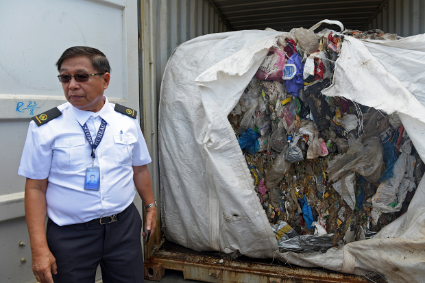 A Philippine customs official stands next to a shipping container filled with garbage that was returned to Seoul after it was shipped to a port in the southern Philippines from South Korea, Jan. 13, 2019. [Froilan Gallardo/BenarNews]