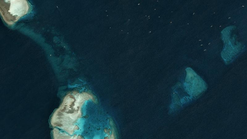 Multiple, unidentified vessels can be seen in the top right-hand corner of this satellite image taken just north of the Chinese-occupied base at South Johnson Reef March 22, 2020. [Planet Labs Inc.]