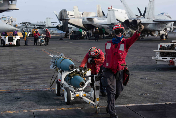 U.S. Navy men transfer bombs from a designated holding location to an aircraft on the flight deck of the U.S. aircraft carrier USS Ronald Reagan, near the disputed region of the South China Sea, Aug. 17, 2019. [Janweb B. Lagazo/U.S. Navy]