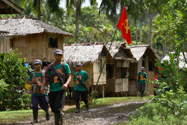 Members of the New People's Army, armed wing of the Communist Party of the Philippines, walk past a hammer-and-sickle flag displayed in a village on the southern island of Mindanao, Dec.26, 2014. [AFP]