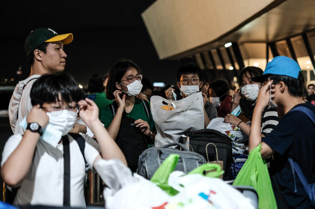 South Korean children on an educational tour in the Philippines are given face masks as a precautionary measure outside Manila's international airport, Jan. 23, 2020.  [Jojo Rinoza/BenarNews]