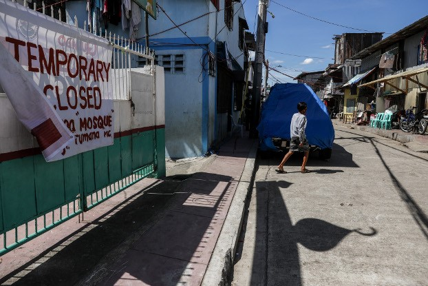 A man walks past a mosque in Manila that is closed during the Muslim holy month of Ramadan, April 24, 2020. (Basilio Sepe/BenarNews)