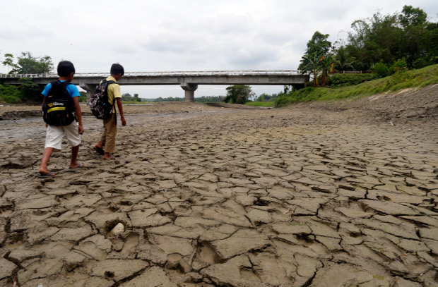 Children walk on a dried up river in Surallah town in the southern Philippine province of South Cotabato, March 29, 2019. [Jeoffrey Maitem/BenarNews]
