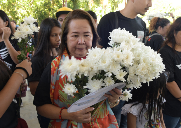 A relative brings a flower offering during a visit at the massacre site in Masalay, Ampatuan town, Maguindanao province, Nov. 18, 2018. [Froilan Gallardo/BenarNews]