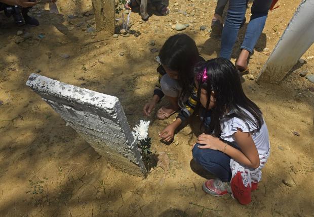 Aya Subang, 9, (left) and a friend visit her father's grave at the Ampatuan Massacre site in Masalay village, Nov. 18, 2018. [Froilan Gallardo/BenarNews]