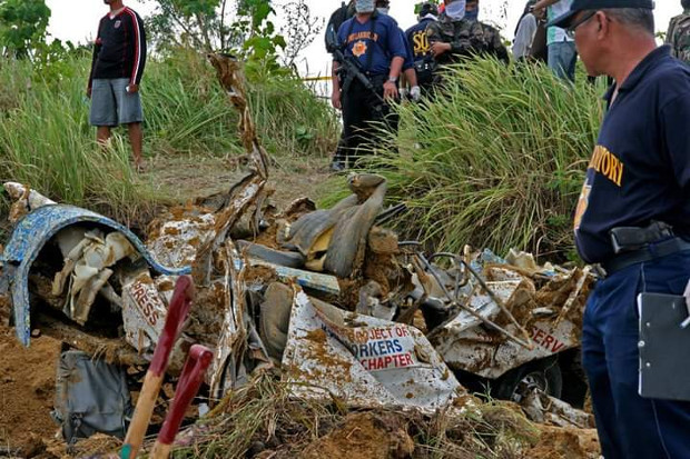 Policemen look at a crushed UNTV news vehicle in the hills of Ampatuan town in the southern Philippines, Nov. 23, 2009. [Nonoy Espina/BenarNews]