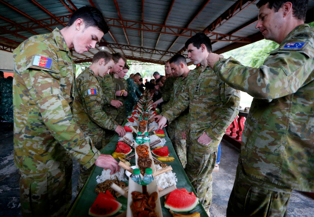 "Australian Defense Force personnel (right) face off against Philippine marines in a ""boodle fight"" following a military exercise at the Gregorio Lim Marine Base in Cavite province, southwest of Manila, Dec. 18, 2017. [AP]"