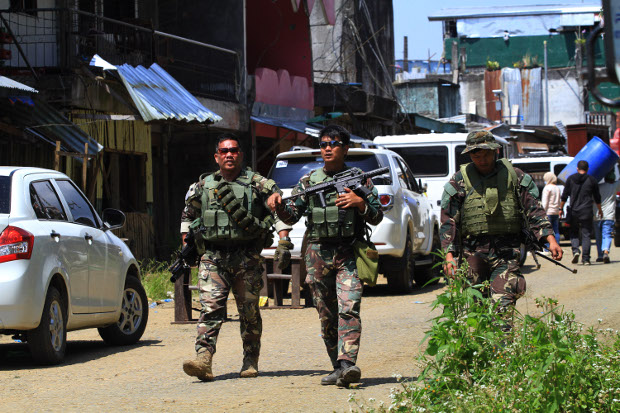 Philippine troops guard hundreds of residents who were allowed to visit their ruined homes in the southern city of Marawi, April 4, 2018. [Richel V. Umel/BenarNews]