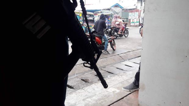 A soldier armed with an assault rifle guards a busy street in the southern Philippine town of Jolo, April 10, 2019. [Mark Navales/BenarNews]