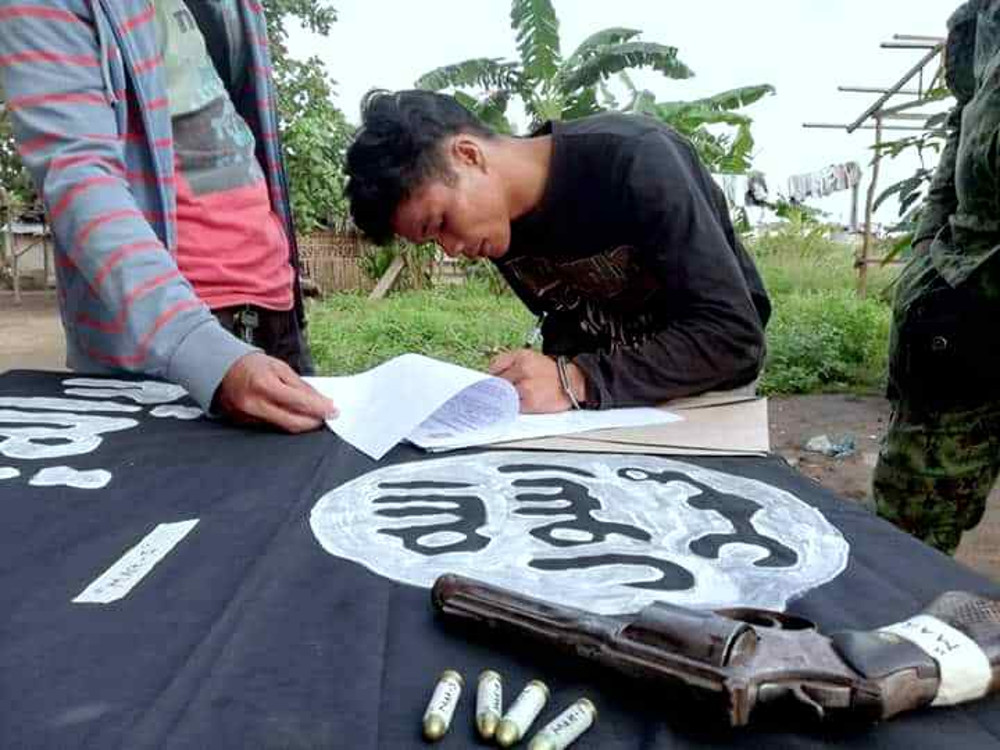 Suspected Filipino militant Jomar Maan signs police documents on a table draped with an Islamic State flag after his arrest in the southern Philippine city of General Santos, Sept. 17, 2019. (Photo: Joseph Jubelag/BenarNews)