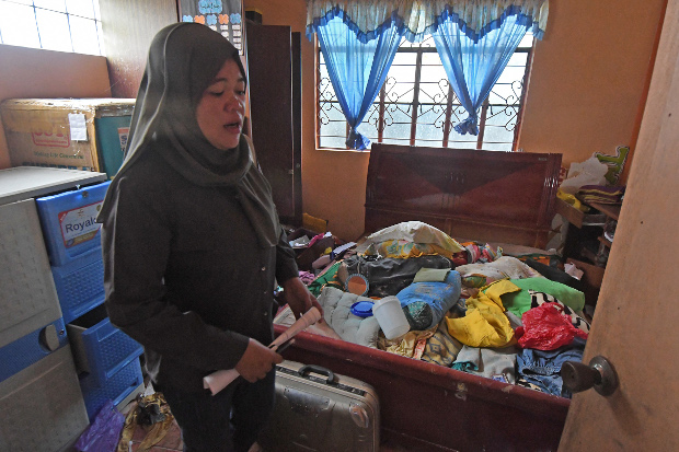 Baicona Hassan is emotional as she looks at a ransacked room in her house in Basak Malotlot, a village in the southern Philippine city of Marawi, Oct. 26, 2017. [Froilan Gallardo/BenarNews]