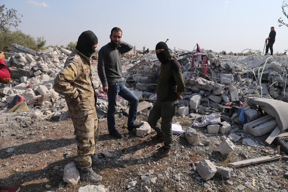 People look at a destroyed house near the village of Barisha in Syria's Idlib province, after a U.S. military operation that killed Islamic State leader Abu Bakr al-Baghdadi, Oct. 27, 2019. (Photo: AP)
