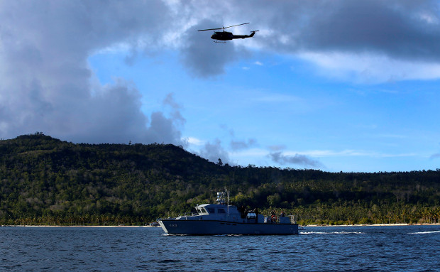 A Huey helicopter flies above a Philippine Coast Guard vessel circling the coastline in the southern Philippine province of Sulu, as state security forces tightened the security to thwart possible attacks by Islamic State militants, Oct. 22, 2019. [Mark Navales/BenarNews]