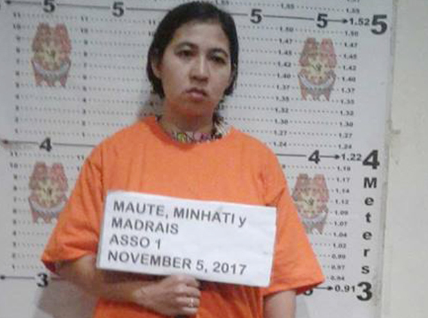 Indonesian Minhati Madrais, widow of slain militant Omarkhayam Maute, holds a sign with her name during her booking at a police station in the southern Philippine city of Iligan following her arrest, Nov. 5, 2017. [Police HO]