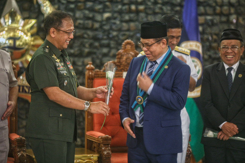 Moro Islamic Liberation Front (MILF) leader Murad Ebrahim smiles as the Philippine military's chief of staff, Gen. Carlito Galvez, offers him a flower during his visit at Camp Aguinaldo in Quezon city, Metro Manila, Nov. 19, 2018. [Luis Liwanag/BenarNews]