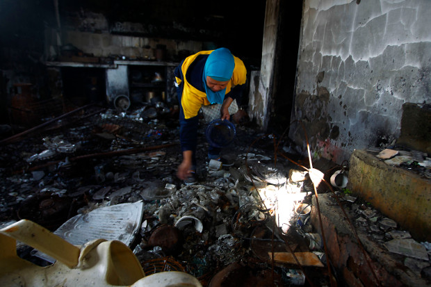 A woman looks for family mementoes to salvage from her home in the southern Philippine city of Marawi, which was flattened by five months of aerial bombings and firefights between government forces and pro-Islamic State militants, Nov. 23, 2017. [Mark Navales/BenarNews]