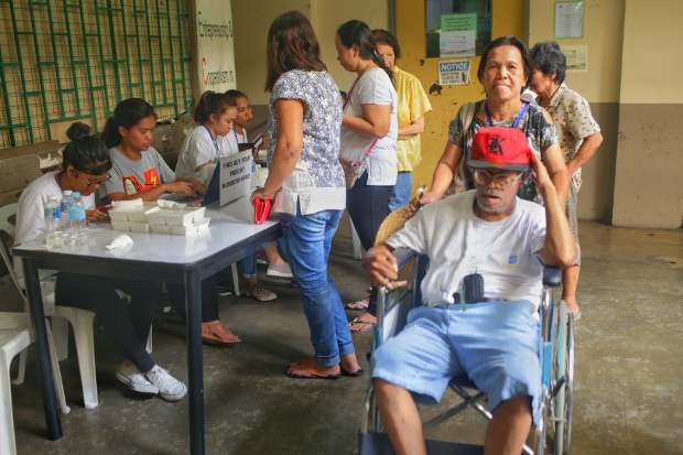 A woman helps a man in a wheelchair after he cast his ballot at a Manila polling precinct, May 13, 2019. [Luis Liwanag/BenarNews]