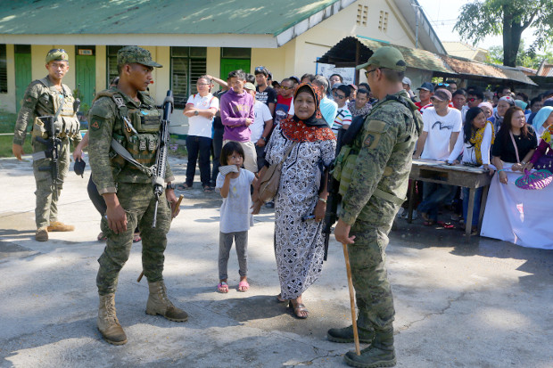 Members of the Philippine Army's 6th Infantry Division provide security as Muslim residents troop to polling centers at a school in Cotabato City's Tamontaka village to cast their votes for the midterm elections, May 13, 2019. [Mark Navales/BenarNews]