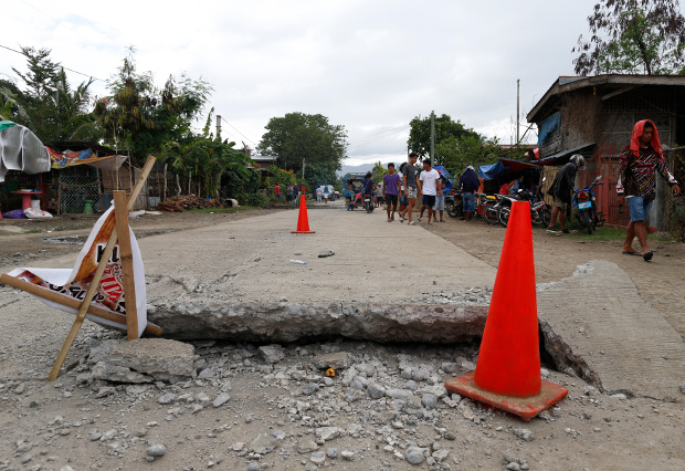 Residents walk along a destroyed road in Padada town in the southern Philippine province of Davao del Sur after a 6.9-magnitude earthquake, Dec. 16, 2019. [Jeoffrey Maitem/BenarNews]