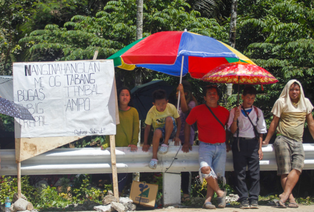 Residents of Makilala, an earthquake-hit town in North Cotabato province in the southern Philippines, stand along a highway and hold signs asking commuters to give them food and water, Nov. 4, 2019. [Jeoffrey Maitem/BenarNews]