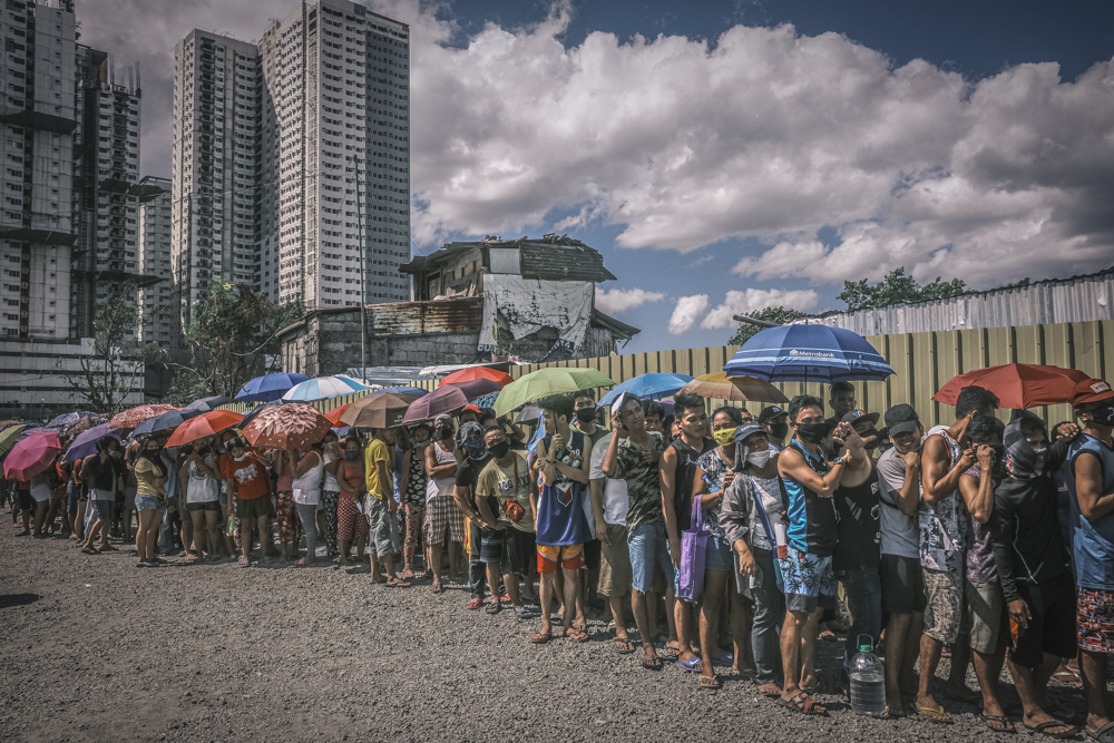 Dozens of people line up in Manila to receive COVID-19 relief supplies, April 2, 2020. Photo: Luis Liwanag/BenarNews