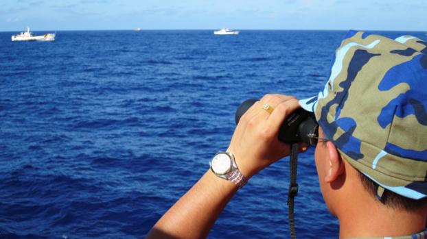 A Vietnamese Coast Guard ship crewman watches Chinese Coast Guard ships follow a Vietnamese ship near a South China Sea oil rig, July 2014. [Reuters]