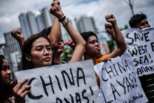 Protesters raise their fists and carry anti-China signs during a protest rally in front of the Chinese Embassy in Manila, April 9, 2019. (Jojo Rinoza/BenarNews)