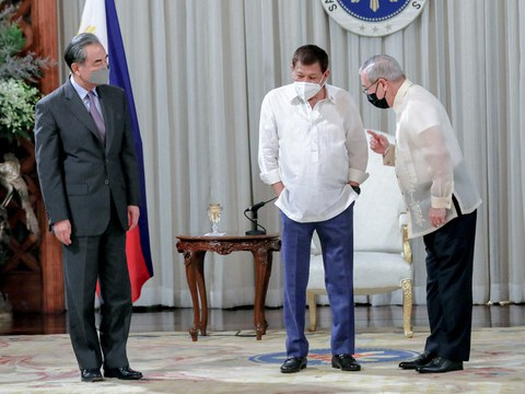 Philippine President Rodrigo Duterte (center) listens to Foreign Secretary Teodoro Locsin as they welcome Chinese Foreign Minister Wang Yi during a courtesy call at the Malacañang Palace in Manila, Jan. 16, 2021.