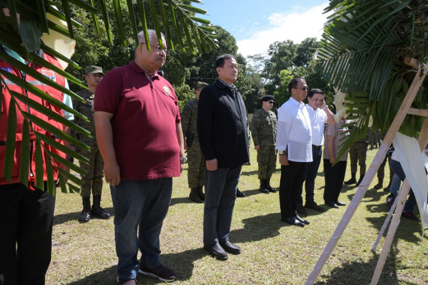 Philippine officials led by Task Force Bangon Marawi chairman Eduardo del Rosario (in black) and Presidential Peace Adviser Carlito Galvez (in white) lay a wreath at a marker in honor of  more than 160 soldiers and police killed during the five months of fighting in Marawi City, Oct. 17, 2019. [Froilan Gallardo/BenarNews]