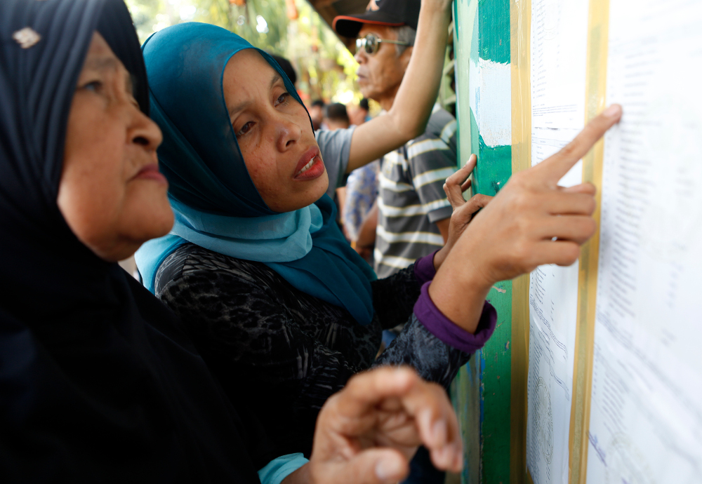 Residents look for their names on a list at a polling center at an elementary school in Sultan Kudurat, Maguindanao province, southern Philippines, as they prepare to vote in a referendum to ratify a law that would give Muslims autonomy in the region, Jan. 21, 2019. [Jeoffrey Maitem/BenarNews]