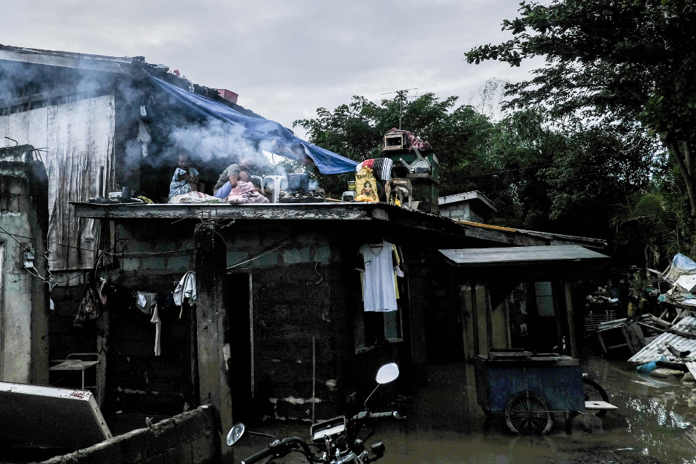 Residents of Linao East, a village in Tuguegarao, Philippines, cook a meal on the roof of their home, Nov. 16, 2020. [Jojo Rinoza/BenarNews]