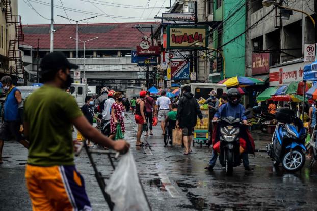 Market goers fill a rain-soaked street at the Blumentritt Markey in Manila, May 15, 2020. [Jojo Rinoza/BenarNews]
