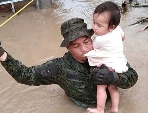 A Philippine soldier rescues a baby in the town of Libmanan, Camarines Sur province, Nov. 12, 2020. [Handout Armed Forces of the Philippines]