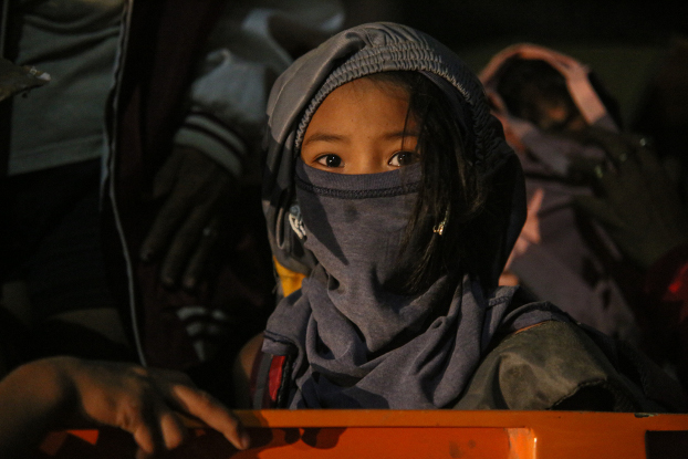 A young girl covers her head and face as her family evacuates from the danger zone near the Taal Volcano, Jan. 12, 2020. [Jojo Riñoza/BenarNews]