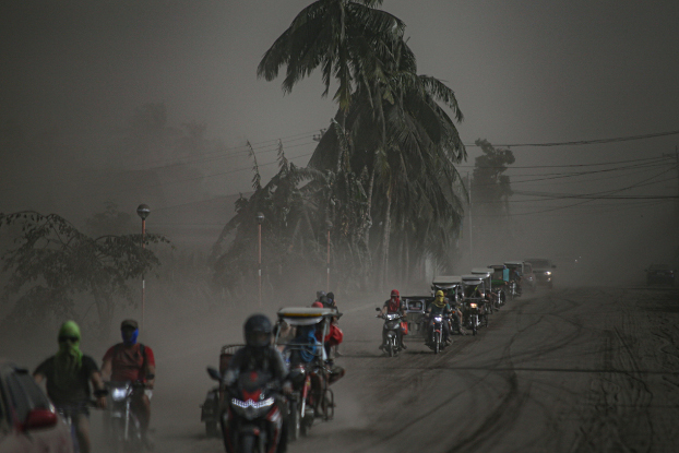 A convoy of motorcycles heads away from Agoncillo town in Batangas province to escape the ash from the Taal Volcano eruption, Jan. 13, 2020. [Jojo Riñoza/BenarNews]