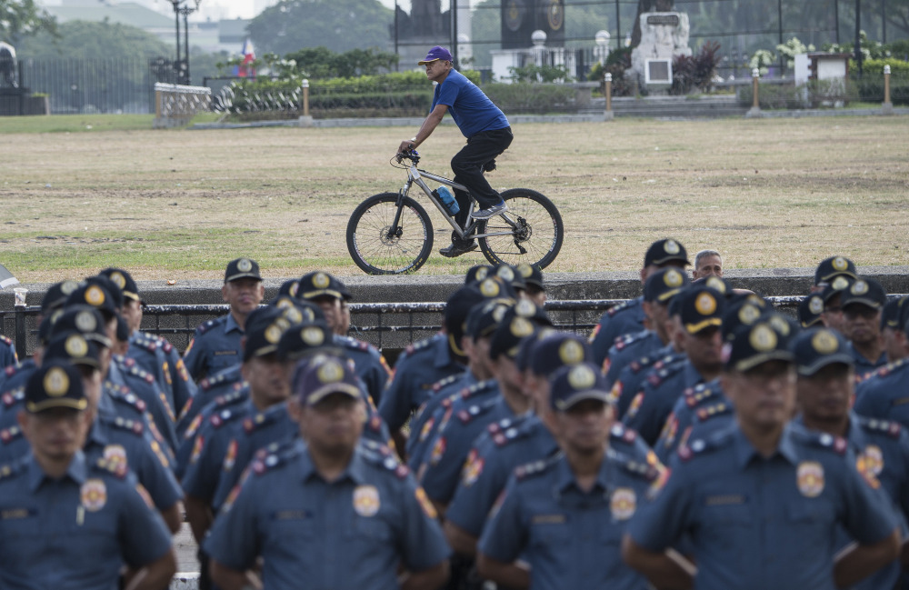 A man rides his bicycle past police standing in formation during an inspection at the police district of Manila, March 16, 2018. (Photo: AFP)