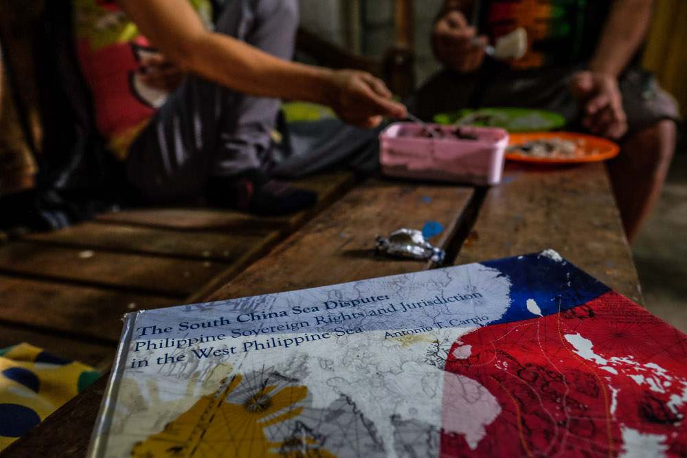 A book about an international court case in a territorial dispute over Scarborough Shoal sits on a bench in Johnny Sonny Geruela's home as he and his wife share a meal, Sept. 6, 2019. [Jojo Rinoza/BenarNews]