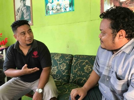 Abdul Kadir Abdjul (left), a local youth leader in Poso, talks his colleague, Indonesia, Nov. 19, 2020. [Keisyah Aprilia/BenarNews]