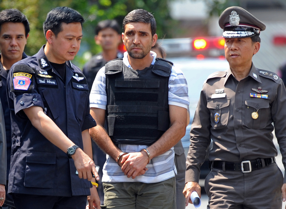 Thai police officers escort Iranian bomb suspect Mohammad Khazaei (center) during an investigation at his rented house in Bangkok, Feb. 20, 2012. [AFP]
