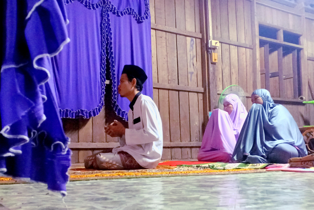 Makoree Abu leads his mother and sister-in-law in Tarawih prayers at his parents' home in Pattani province. April 24, 2020.